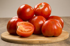 Some tomatoes over a wooden background. Fresh vegetable stock image