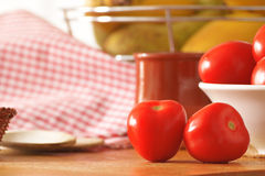 Some tomatoes on a wooden table of a rustic kitchen while cooking. Natural ingredients. Copy space for editor's text Stock Photos
