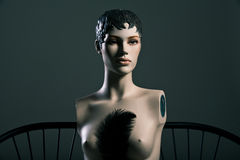 Some topless female mannequin with pen. The upper part of the body of the female mannequin without arms, topless with a pen on a dark background royalty free stock image