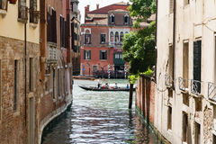 Some tourists enjoy a trip in a gondola, along a canal in Venice. VENICE, ITALY - JUNE 4, 2016 - Some tourists enjoy a trip in a gondola, along a canal in Venice royalty free stock photography