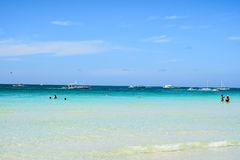 Some tourists swim and take pictures in the White Beach of Borac. BORACAY, PHILIPPINES - JANUARY 7 , 2015 - Some tourists swim and take pictures in the White Royalty Free Stock Image