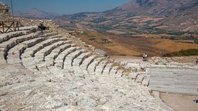 Some tourists visit the ruins of the ancient Greek theater of Se. SEGESTA, ITALY - AUGUST 30, 2017: Some tourists visit the ruins of the ancient Greek theater of royalty free stock photos