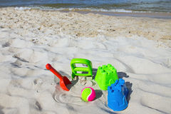 Some toys at the beach. Colourful toys and a ball laying in the sand of a beach stock image