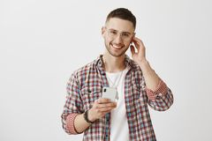 Some tracks meant to be listened with earphones. Portrait of joyful good-looking male with charming smile and trendy. Glasses, holding smartphone, touching Stock Photo