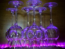 Some transparent glasses illuminated by a purple light. Some transparent glasses in a bar, illuminated by a purple light on a wooden background Stock Photos