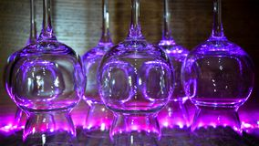 Some transparent glasses illuminated by a purple light. Some transparent glasses in a bar, illuminated by a purple light on a wooden background stock image
