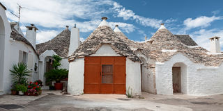 Some Trulli houses in a street of Alberobello, Puglia, Italy. Some Trulli houses in a street of Alberobello in a panoramic view, Puglia, Italy royalty free stock photo
