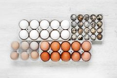 Some types of eggs in the packages. Some kindes of eggs in the packages on the white wooden table stock photos