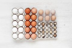 Some types of eggs in the packages. On the white wooden table Stock Image