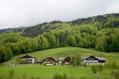 Some typical Austrian houses in the foot of the alps. Typical wooden houses in the Austrian alps. They have three stories an sloping roofs. Behind them are stock photography