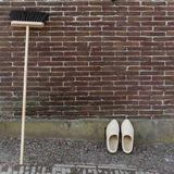 Some typical dutch wooden stuff, clogs and a broom royalty free stock photography