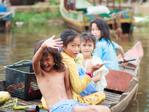Some unidentified children greet tourists from a boat. In the floating village of Kompong Phluk on October 21, 2015 in Kompong Phluk, Cambodia Royalty Free Stock Image