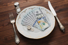 Some US dollars servered like a meal in the vintage plate. US dollars notes and coins shooted like a meal in an old plate with silverware and salt shaker on the stock image