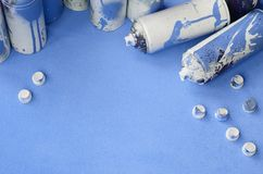 Some used blue aerosol spray cans and nozzles with paint drips lies on a blanket of soft and furry light blue fleece fabric. Class. Ic female design color royalty free stock image