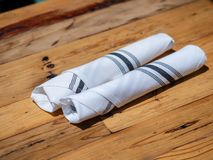 Utensils rolled up in napkin for diners at an outdoor restaurant. Some utensils rolled up in napkin for diners at an outdoor restaurant in the sunshine Stock Photography