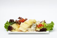 Some vegetables and pieces of cheese. Some vegetables and pieces of cheese on white plate isolated on white background stock image
