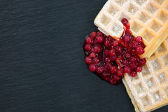 Some waffles with cranberries on a dark slate with powdered suga. R and copyspace Royalty Free Stock Photography