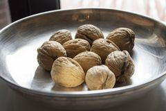 Some walnuts on metal plate. On the table Stock Photos