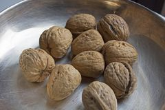 Some walnuts on metal plate. On the table Stock Image