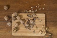 Walnuts. Some walnuts split on a wooden table Stock Photos
