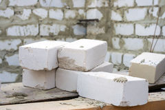 Some white bricks on construction site. Some white bricks with background of building wall Royalty Free Stock Images