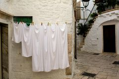 Some White Flat Sheets among Traditional Buildings in the City o. F Locorotondo, in Italy, in Summer on Blur Background stock images