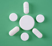 Some of White pills. On a green background Royalty Free Stock Photography