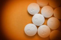 Some white pills aligned. On orange background Stock Images