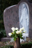 Roses on a grave. Some white roses on a grave with holy mary in the background Royalty Free Stock Photos