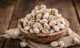 Some whole Pistachios. (selective focus; close-up shot) on wooden background stock photo