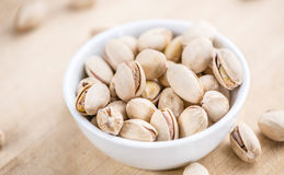 Some whole Pistachios. (selective focus; close-up shot) on wooden background stock photos