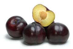 Some whole plums and one half. Some whoe plums and one half isolated on the white background Stock Images