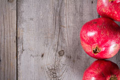 Some whole red pomegranate on rustic wooden unpainted table Stock Photo