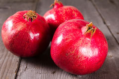 Some whole red pomegranate on rustic wooden unpainted table Royalty Free Stock Images