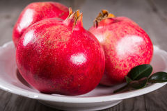 Some whole red pomegranate on rustic wooden unpainted table Stock Image