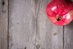 Some whole red pomegranate on rustic wooden unpainted table Royalty Free Stock Image