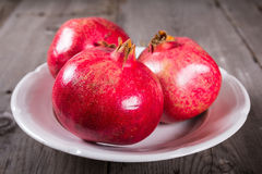 Some whole red pomegranate on rustic wooden unpainted table Royalty Free Stock Photo