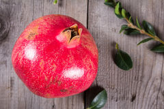 Some whole red pomegranate on rustic wooden unpainted table Royalty Free Stock Photos