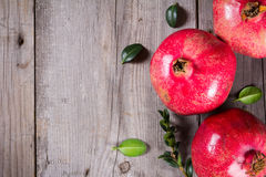 Some whole red pomegranate on rustic wooden unpainted table Royalty Free Stock Photography