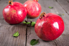 Some whole red pomegranate on rustic wooden unpainted table Stock Images