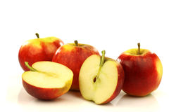 Some whole and some cut red and yellow apples. On a white background royalty free stock photo