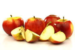 Some whole and some cut red and yellow apples. On a white background Stock Photos