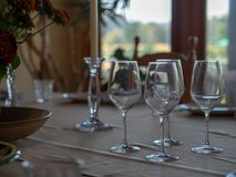 Wineglasses and tableware sitting on a table at a family dinner in a home stock images