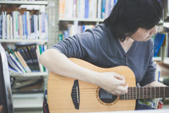 Some woman playing guitar at library on June 18, 2017 in Bangkok TH Royalty Free Stock Image