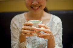 Some woman in white dress holding hot green tea cup with her smile feel relaxation. Royalty Free Stock Photos