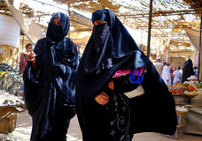 Some women with veil and burqain the souk of the city of Rissani in Morocco. Rissani`s souk is an authentic market at the doorstep of the desert, a traditional Stock Photos