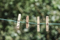 Wooden clothes pegs hanged on rope at garden. Some wooden clothes pegs hanged on rope at garden in spring royalty free stock photos