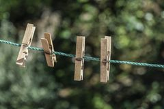 Wooden clothes pegs hanged on rope at garden. Some wooden clothes pegs hanged on rope at garden in spring royalty free stock image