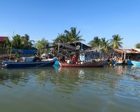 Some wooden fishing boats on front of a traditional village Stock Images