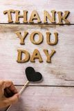 Wooden letters forming the text thank you day. Some wooden letters forming the text thank you day on a rustic wooden surface and a heart attached to a stick in Stock Photos